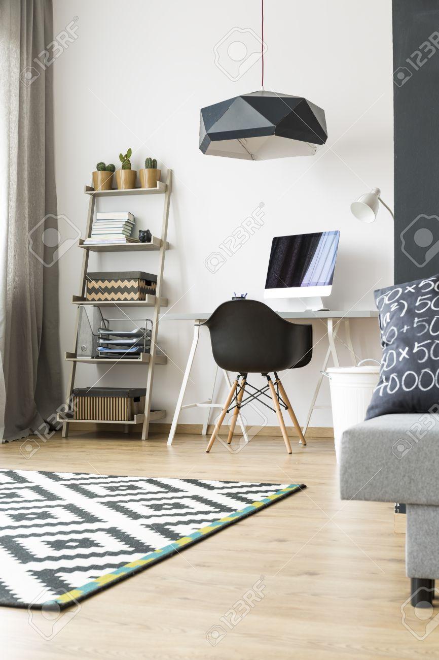 Tir d\'une chambre d\'étudiant avec un bureau minimaliste, un tapis noir et  blanc