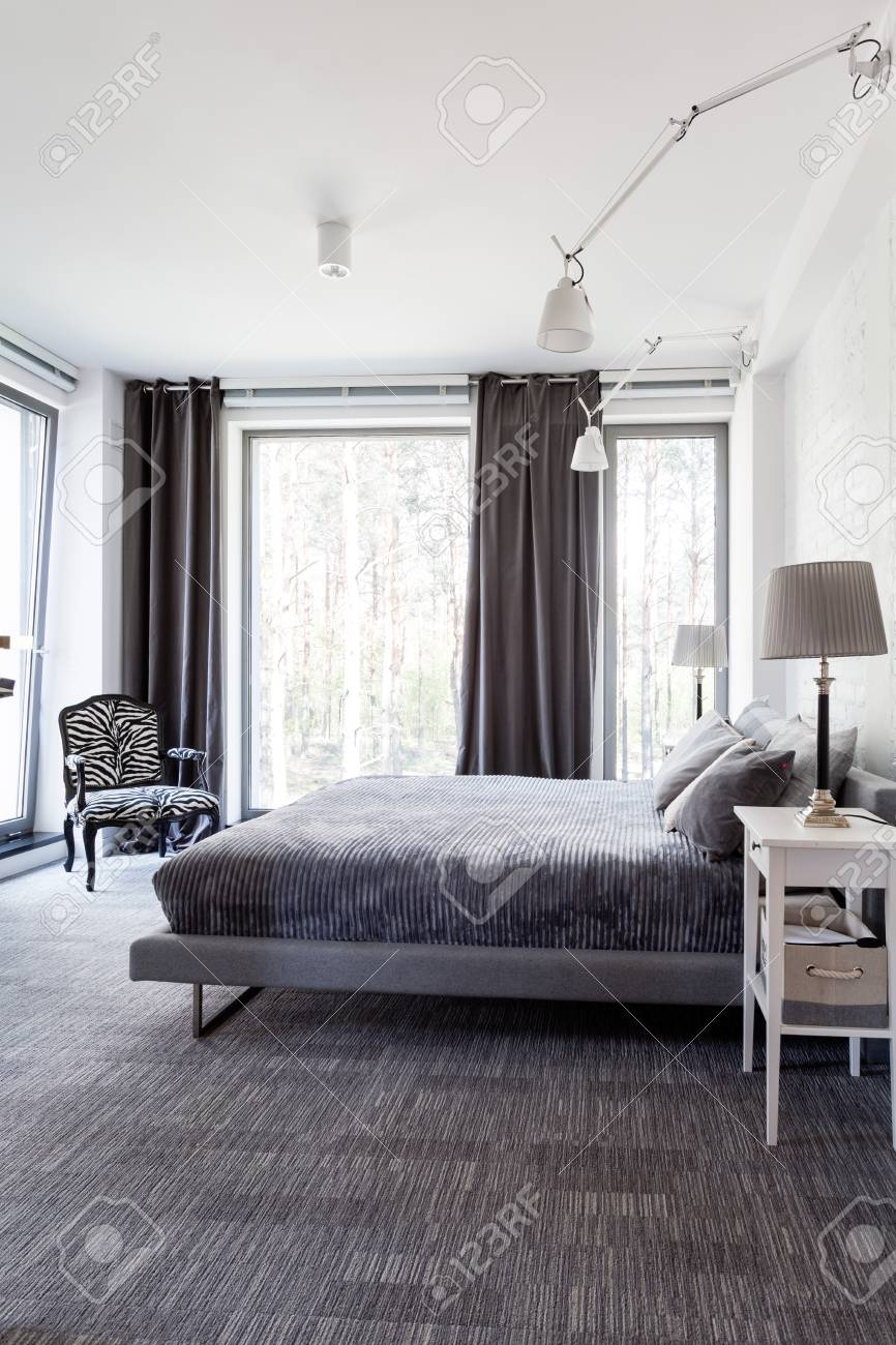 Grey and white modern bedroom with big windows