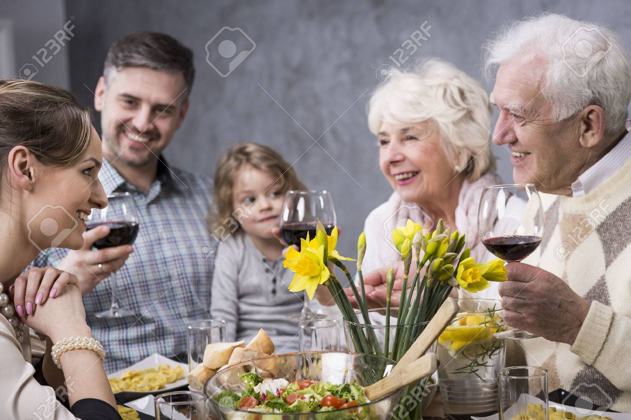 Three generations of the family are involved in a discussion during family dinner - 61274240