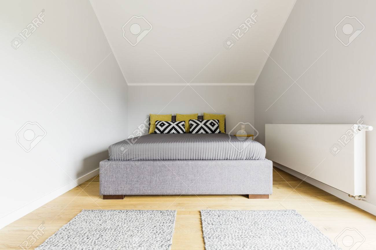 Small But Stylish Attic Bedroom With A Large Grey Bed White Stock Photo Picture And Royalty Free Image Image 61589749