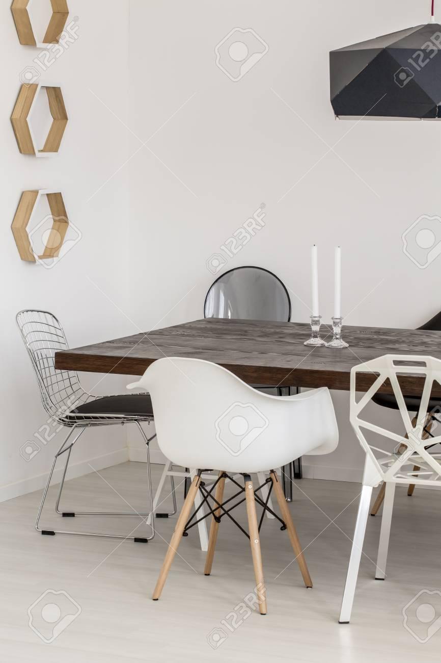 Fragmento de un comedor contemporáneo con mesa de madera maciza y sillas  únicas
