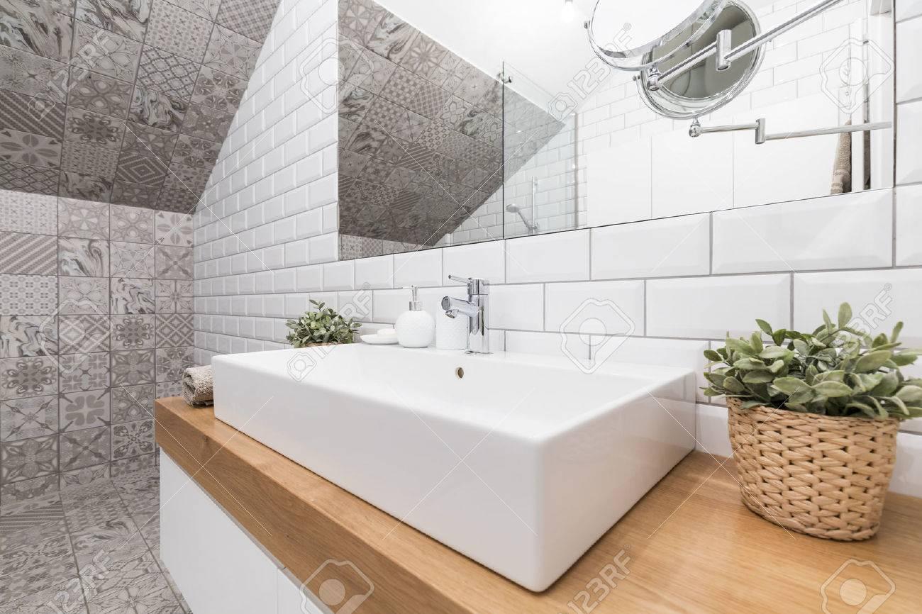 Contemporary bathroom corner with decorative tiles and a rectangular ceramic sink - 61587109