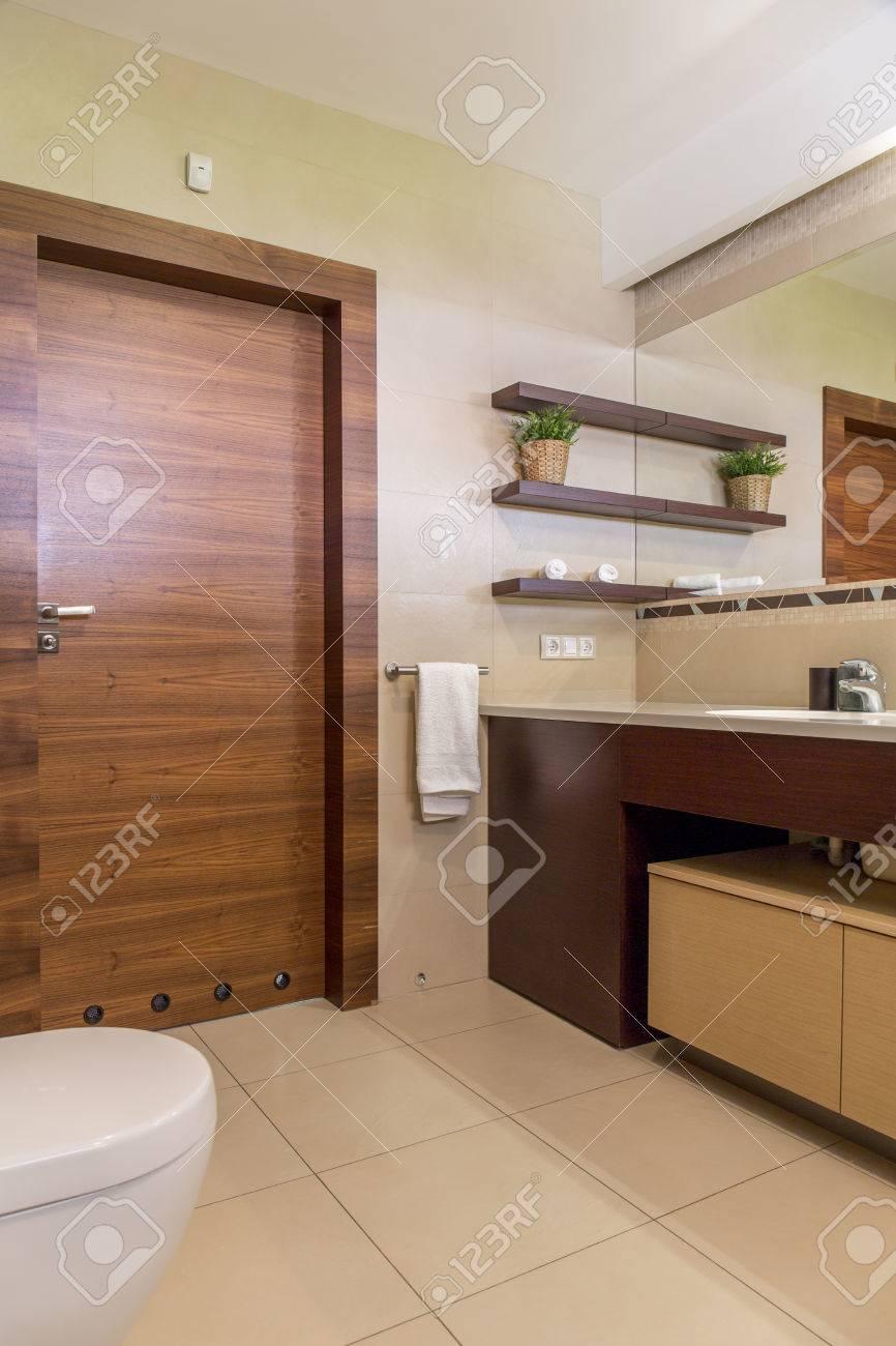 Modernes Badezimmer In Beige, Mit Holztür Und Fliesenboden Standard Bild    61585510