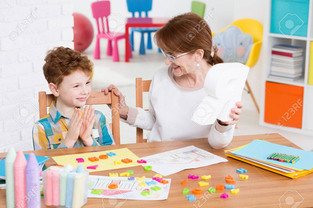 Red-haired boy satisfied with the alphabet learning with the speech therapist Standard-Bild - 61811073