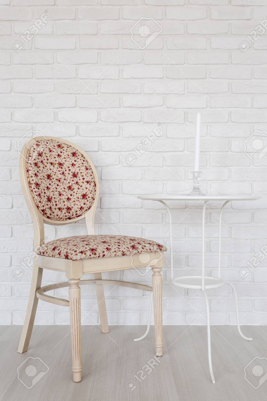 Upholstered Chair And Small Table Standing In Light Interior Stock