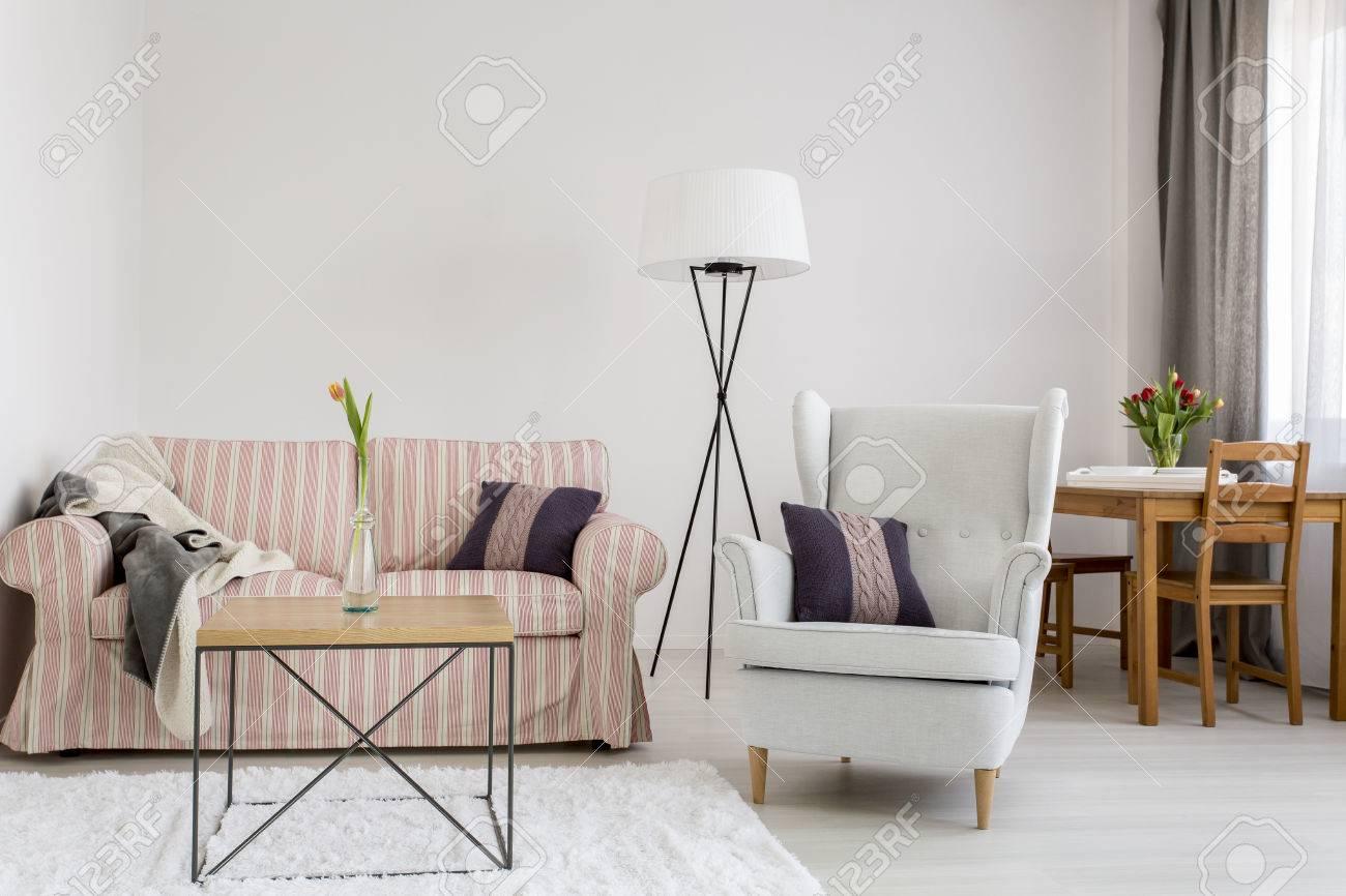 Luz interior con sofá tapizado modelo, cómodo sillón, mesa de comedor con  sillas en el fondo