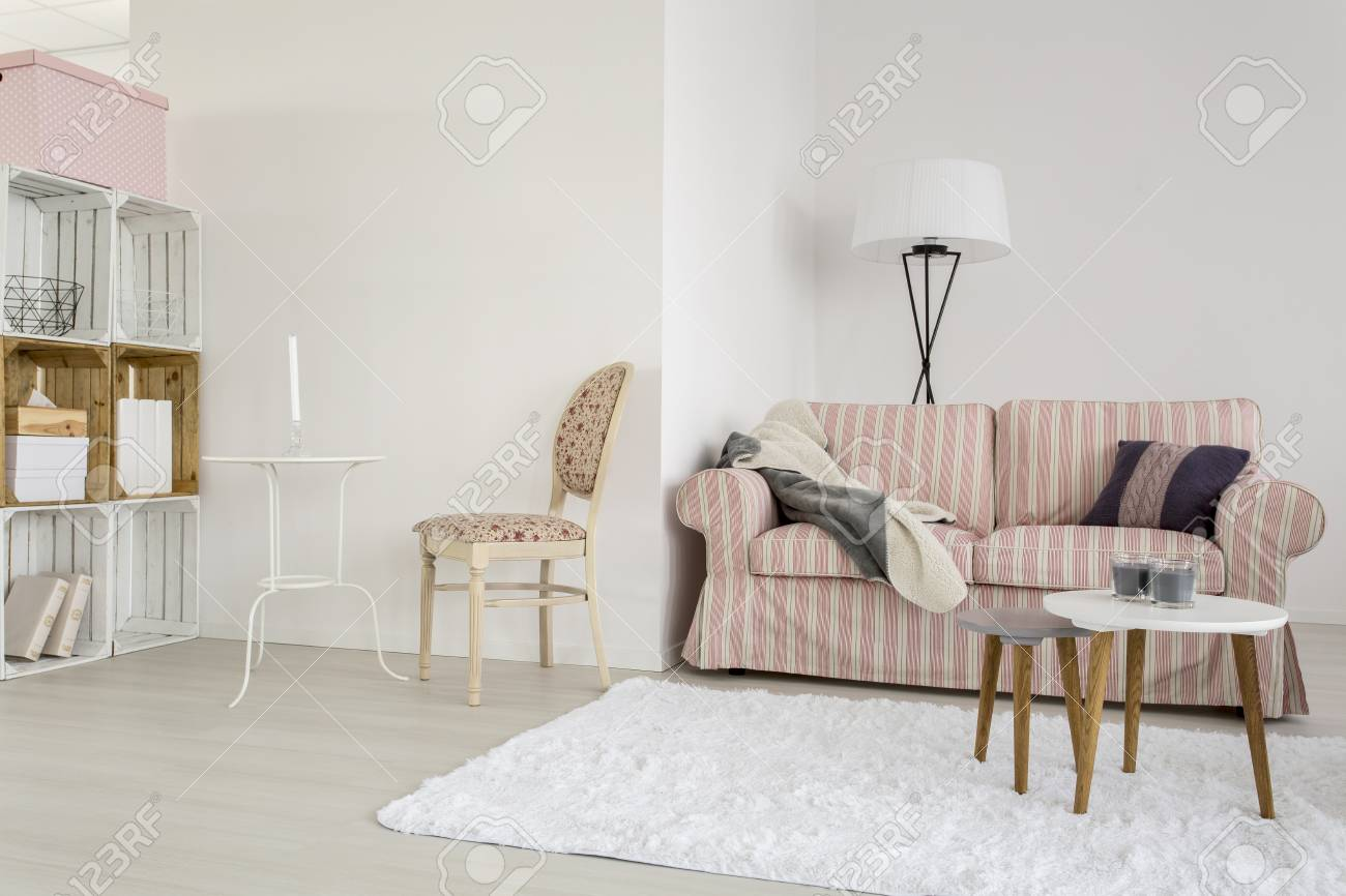 Light living room with upholstered sofa chair and handmade wooden regale stock photo 61865955