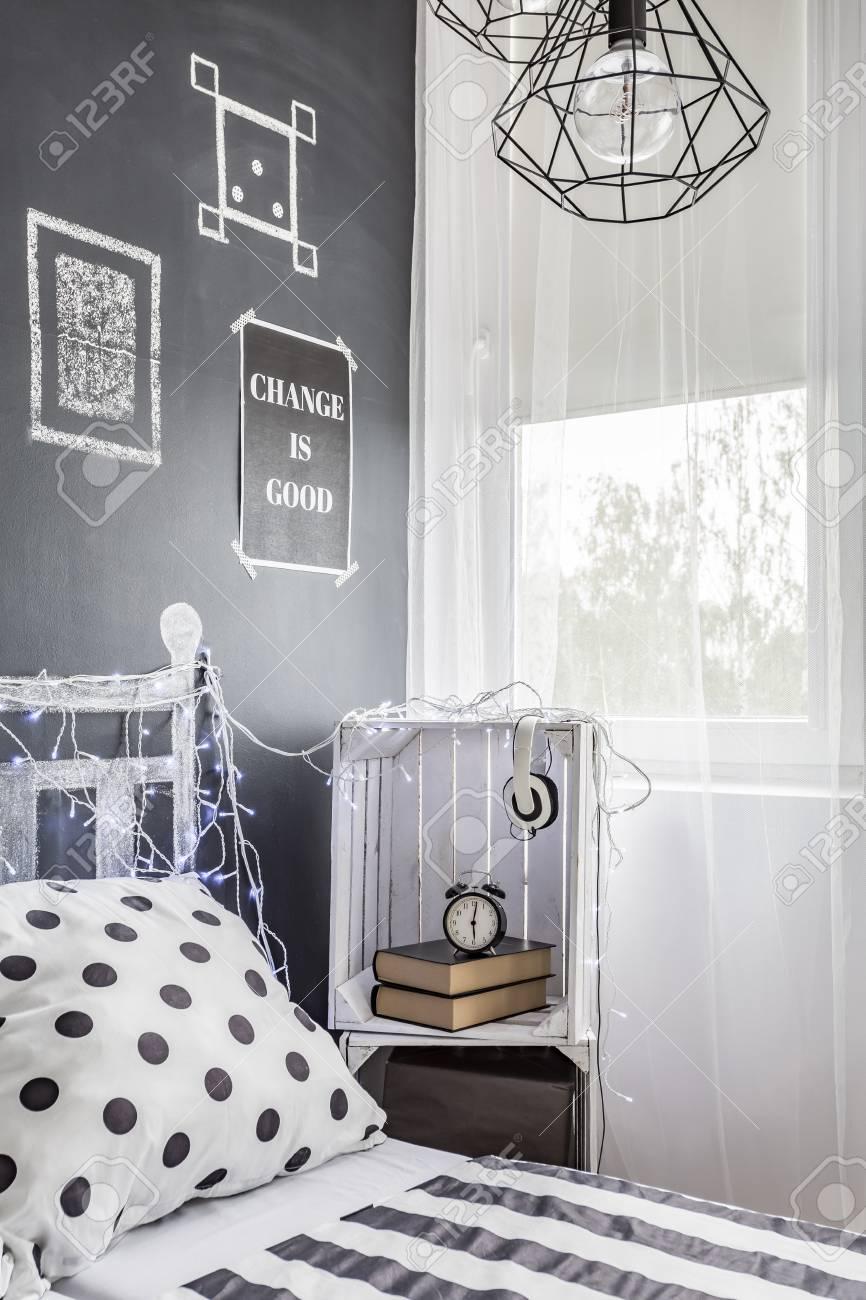 chambre sombre avec fenêtre, table de chevet diy et mur de tableau