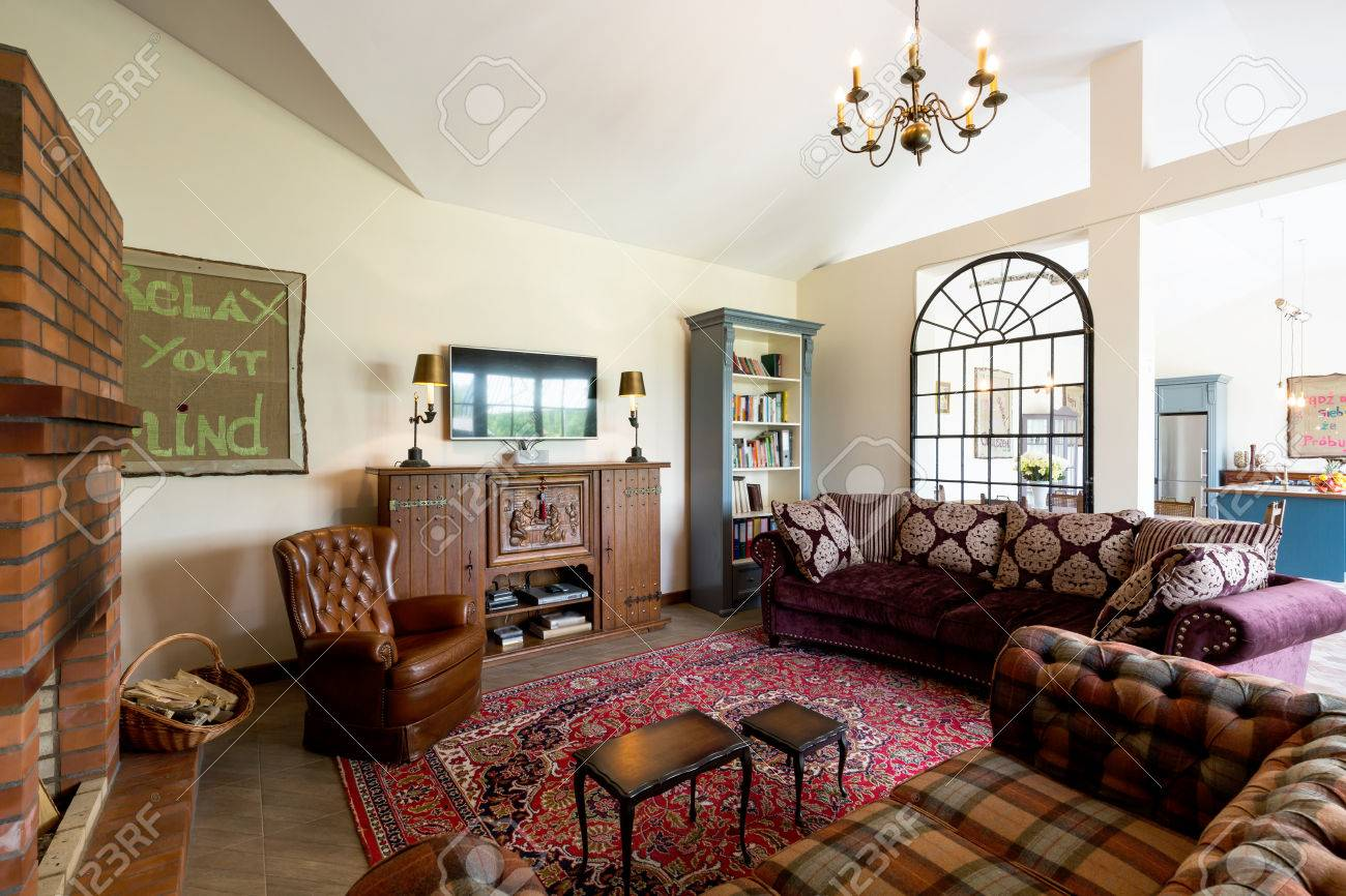 Spacious living room interior in cottage style with checked sofas,..