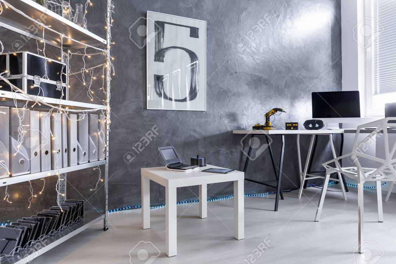 New Style Study Room With Decorative Wall Finish In Grey And Trendy White  Furniture Stock Photo