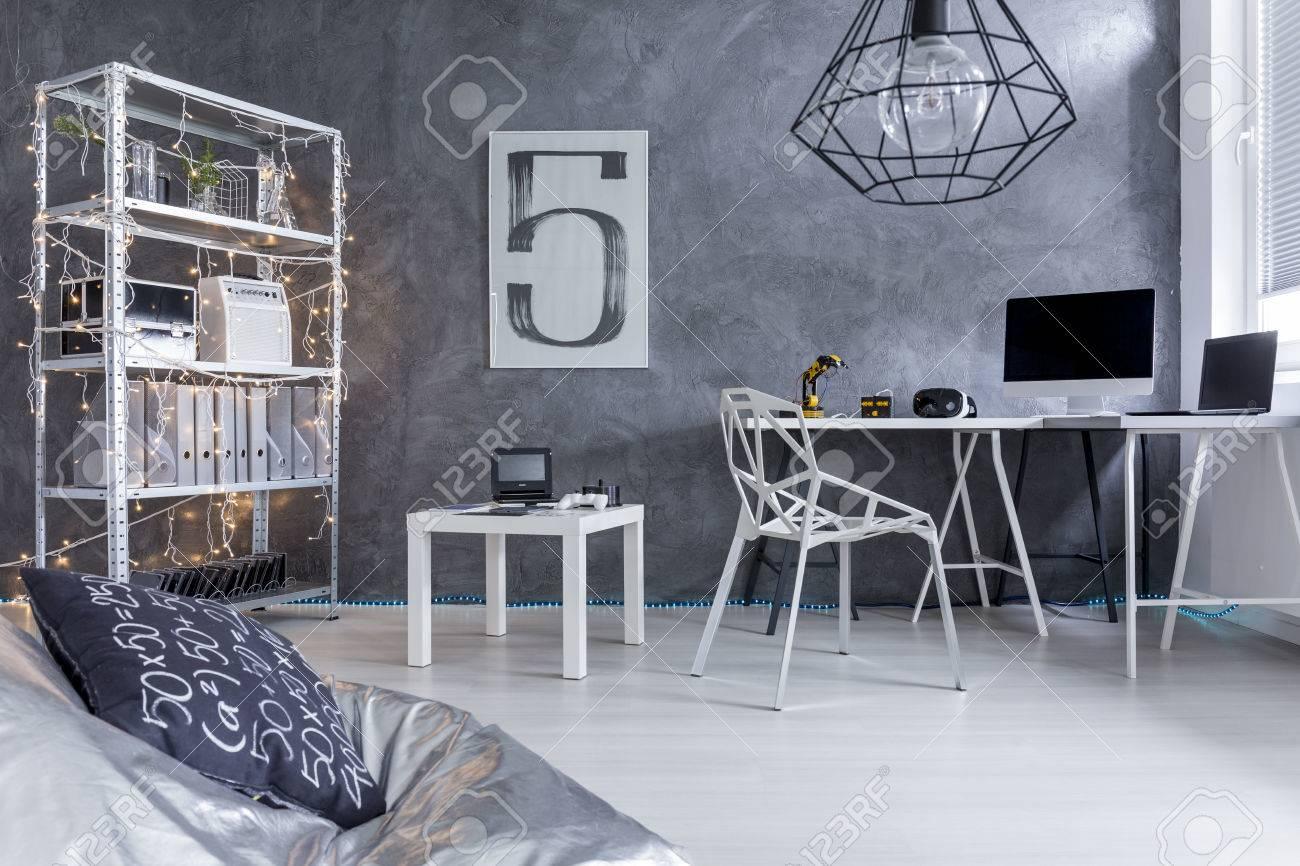Cette chambre moderne avec mur gris pl tre unité de stockage