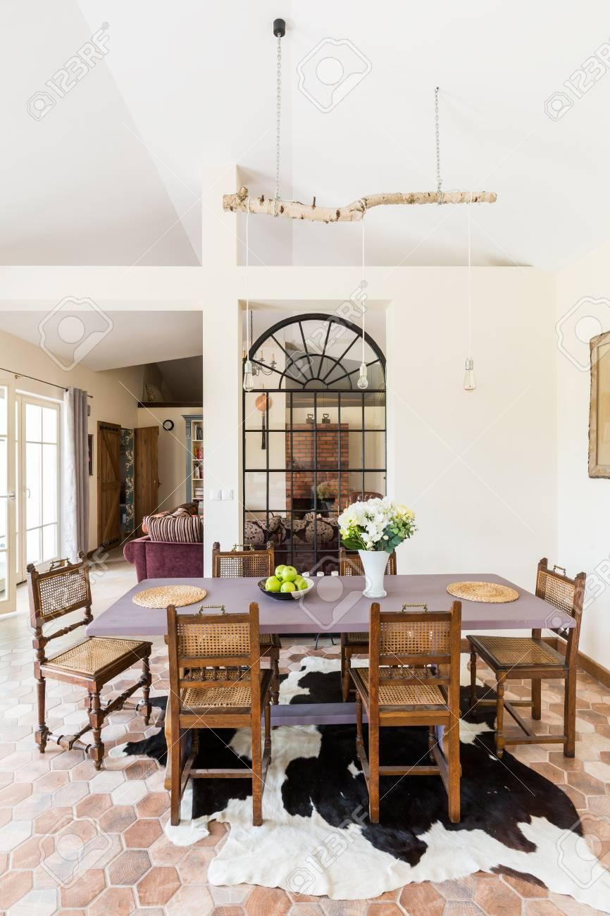 Espaciosa área de comedor con mesa y sillas de madera, alfombra asimétrica  y entrada al patio