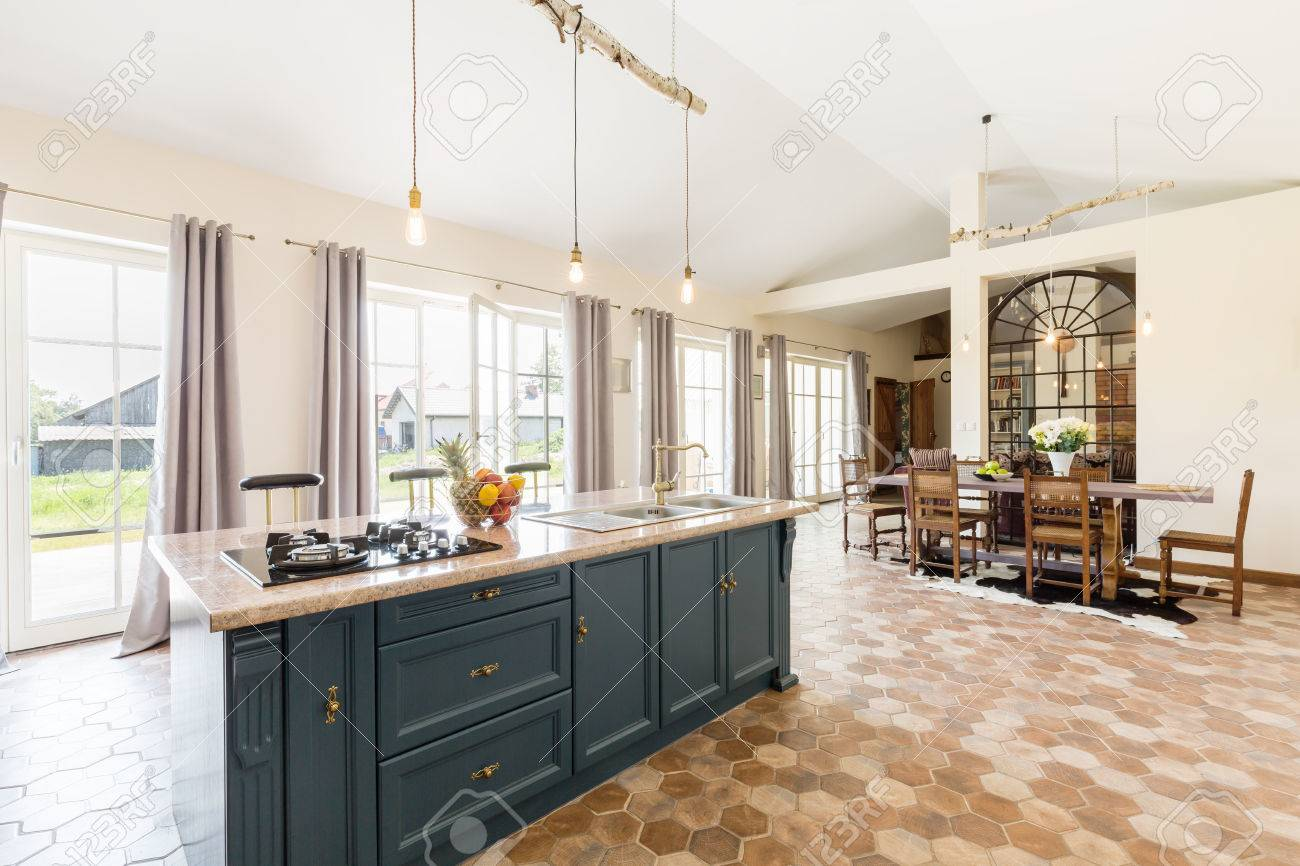 Intérieur de cuisine moderne avec îlot de cuisine au milieu, une table et  des chaises dans une salle à une partie d\'un espace et de nombreuses ...