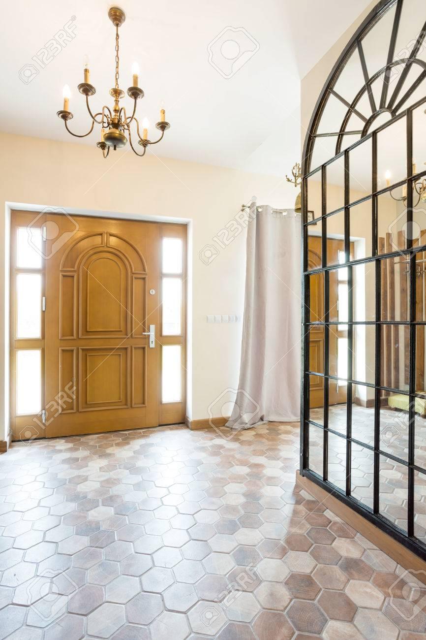 Grand Miroir D Entrée couloir spacieux avec grand miroir sur le mur, la porte d'entrée en bois et  un lustre