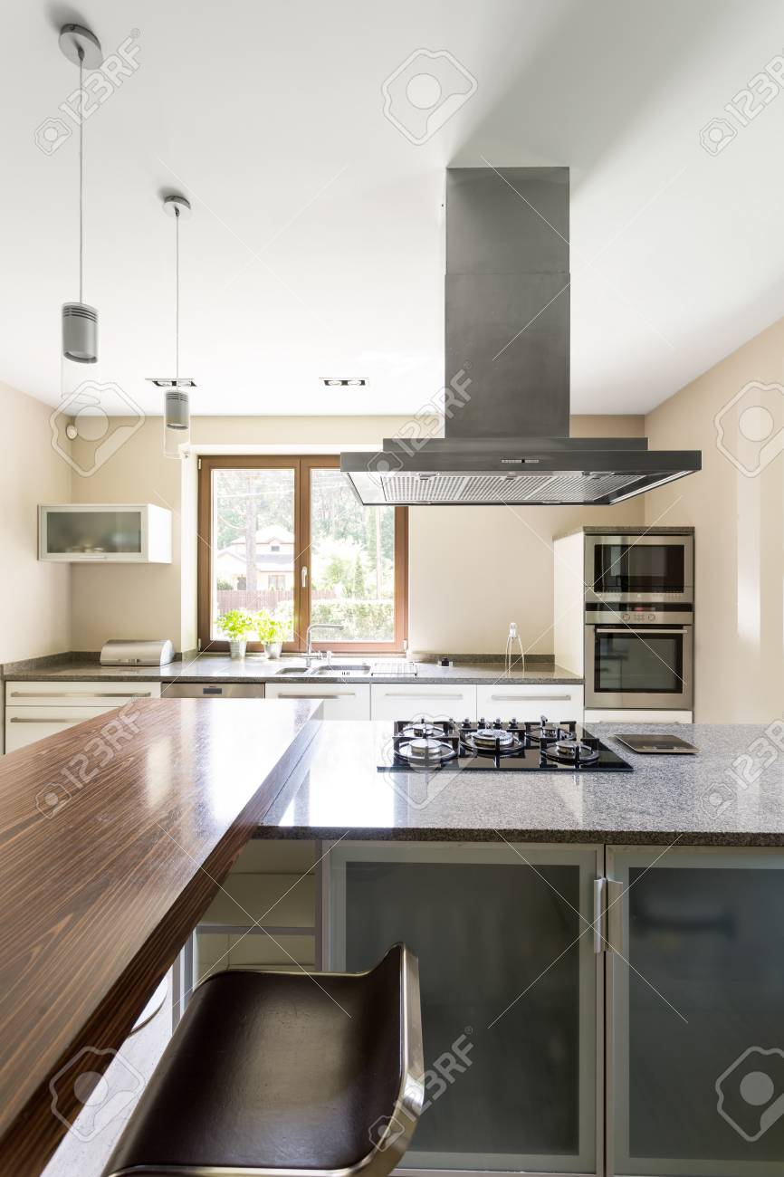 Spacious and minimalist kitchen with marble kitchen top and chrome..