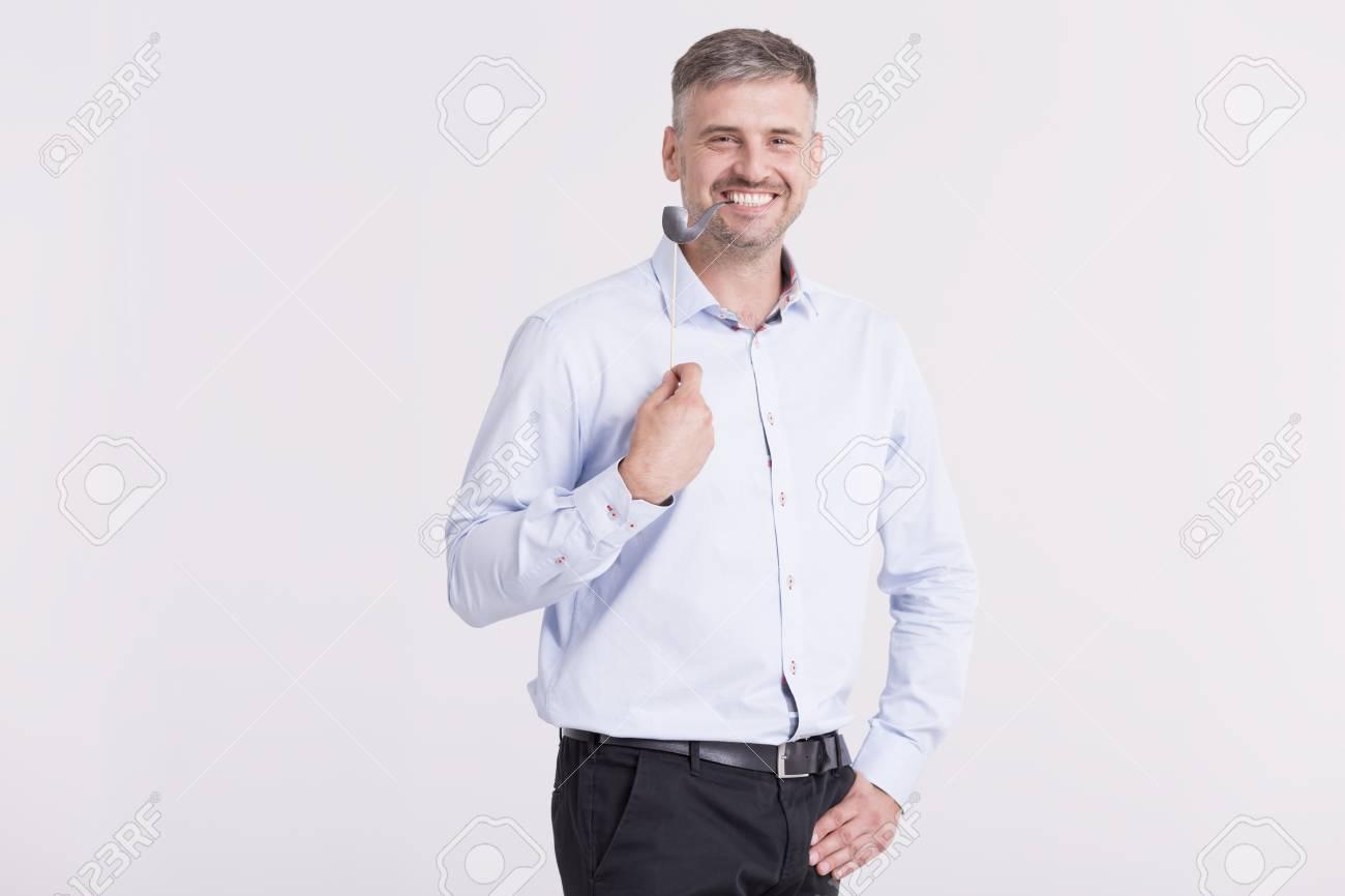 Homme Souriant prise de vue d'un homme souriant beau tenant une pipe de papier sur