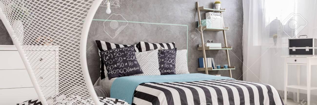 Camera da letto moderna progettata con letto, comò e la parete ciano sullo  sfondo
