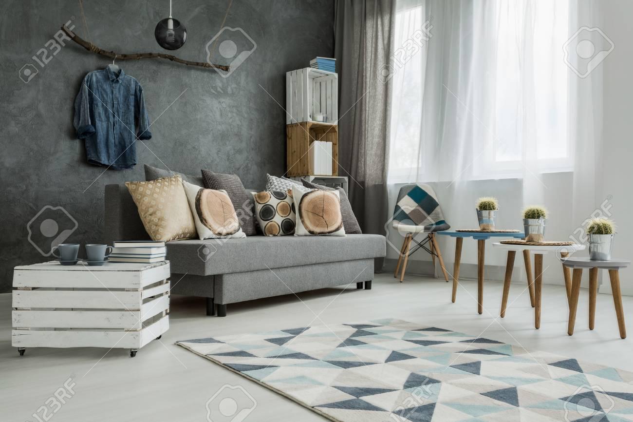 Moderno minimalista e luminoso soggiorno in tonalità di ciano con divano,  poltrona, tre tavolini, tappeti e borlande fatte di casse di legno