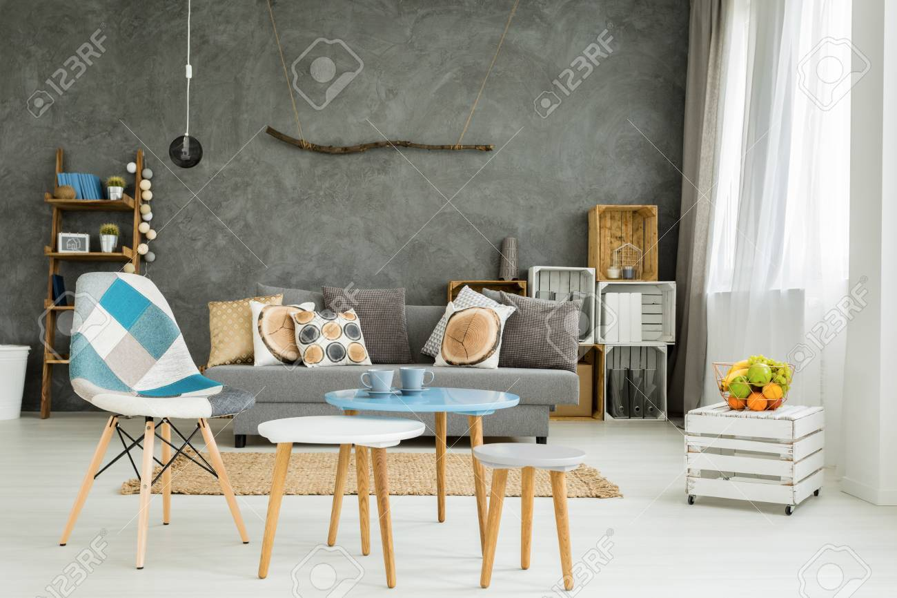 Moderno soggiorno minimalista e luminoso nei toni del ciano con divano,  sedia, tre tavolini da caffè, moquette e bancarella in casse di legno