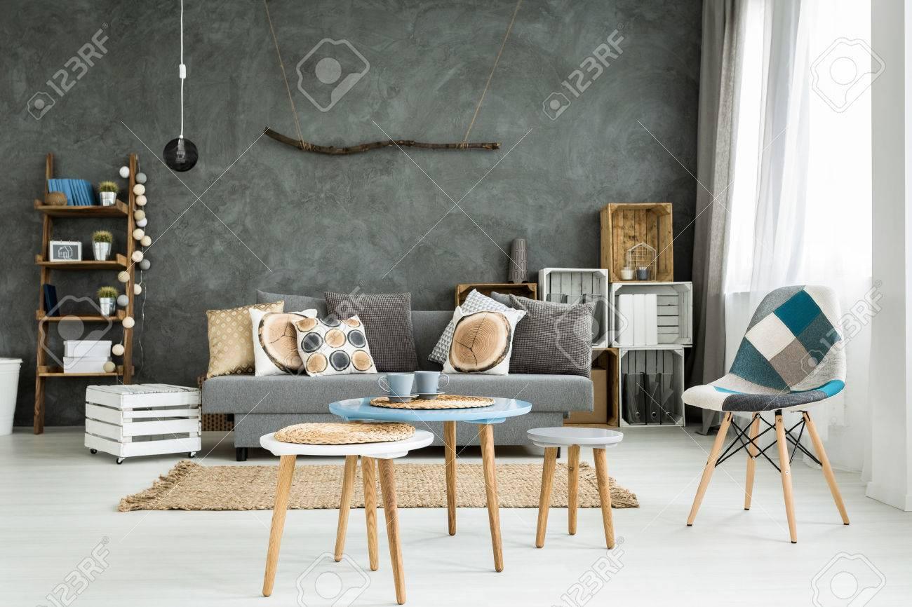 Moderno minimalista e luminoso soggiorno in tonalità di ciano con divano  pieno di cuscini, sedie, tre tavolini, tappeti e borlande in casse di legno