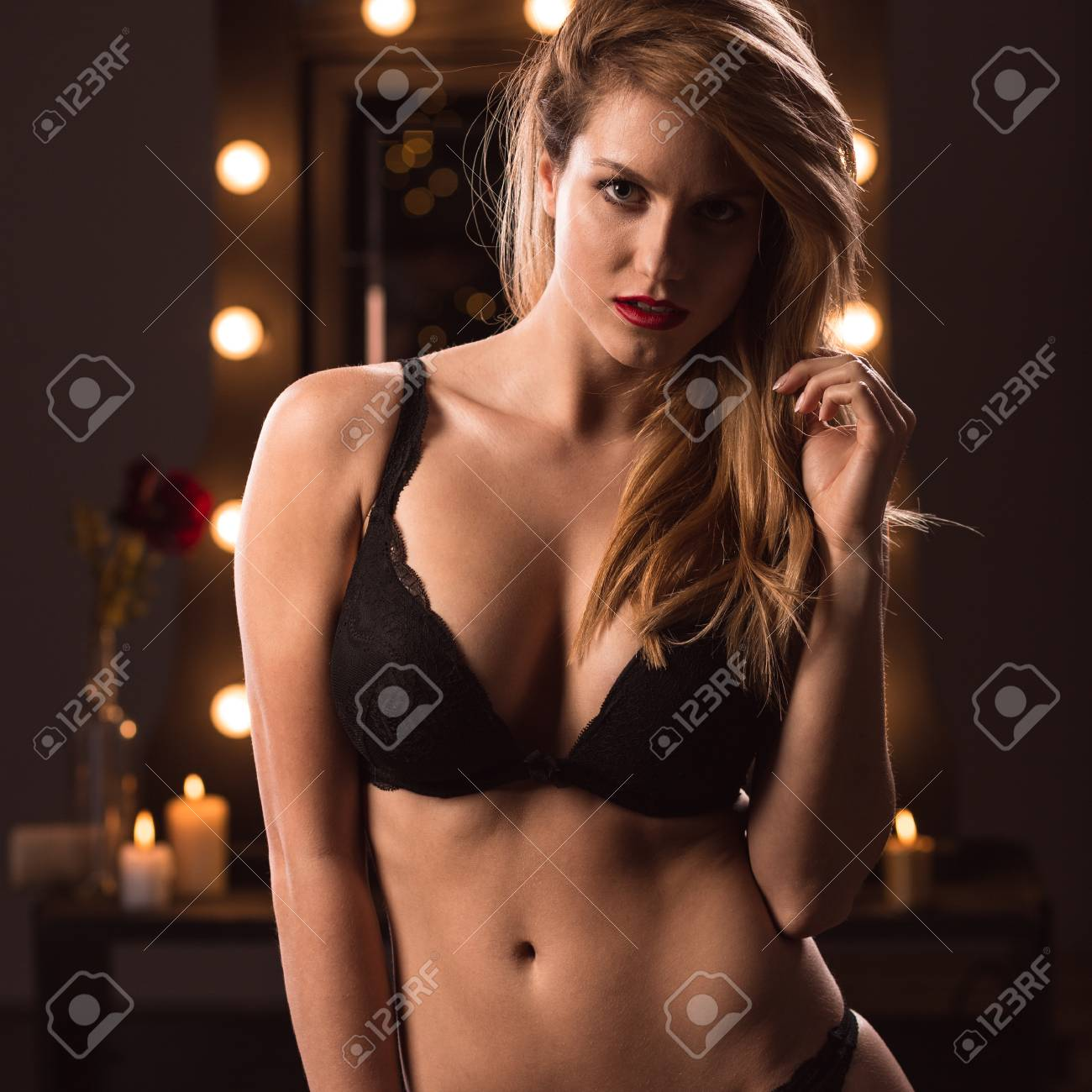 sexy provocative blonde girl tempting and undressing stock photo