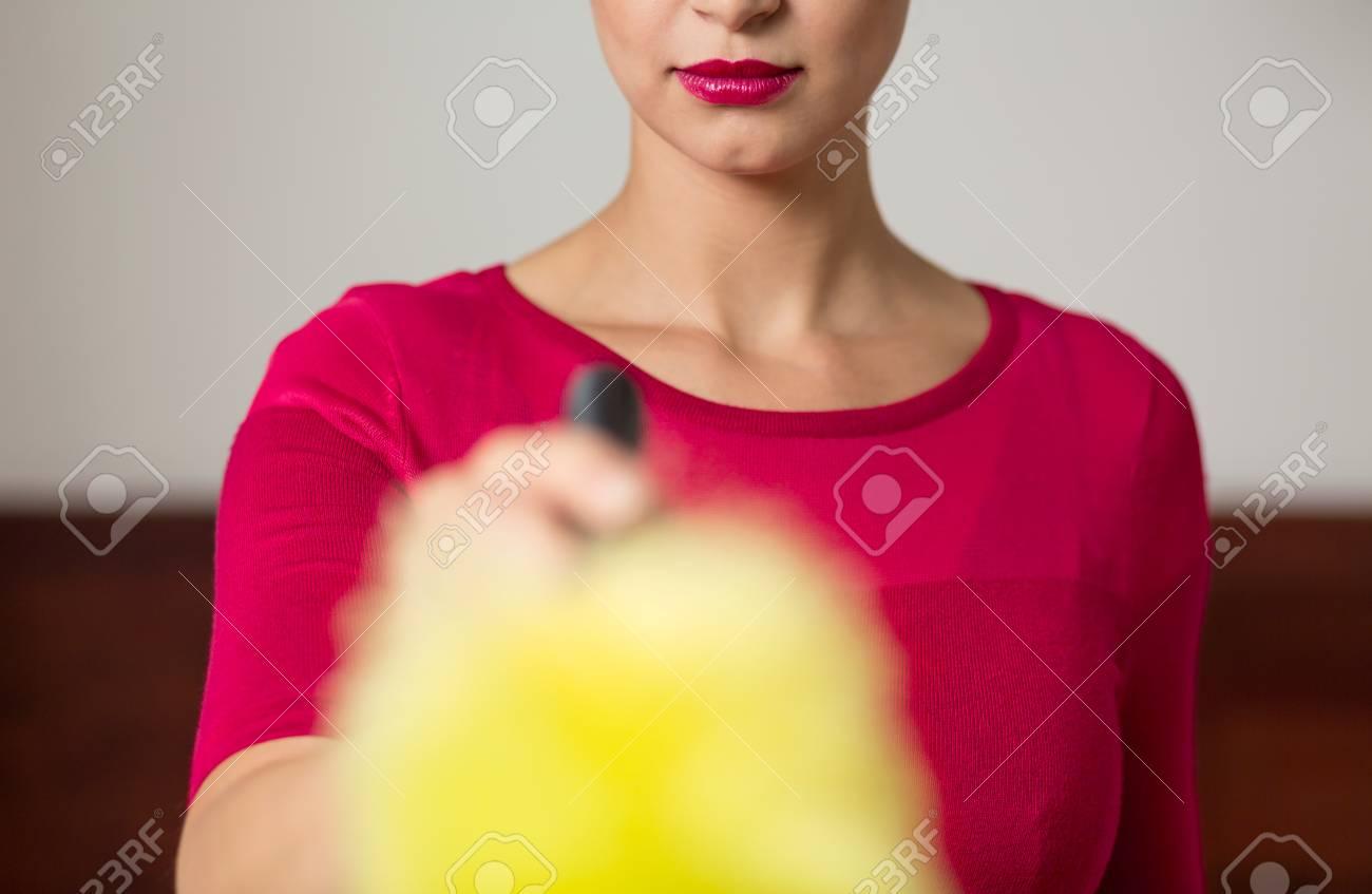 Más Cerca De Tiro De La Mujer Vestida De Color Rosa Mantener El Cepillo Para Polvo En Su Mano