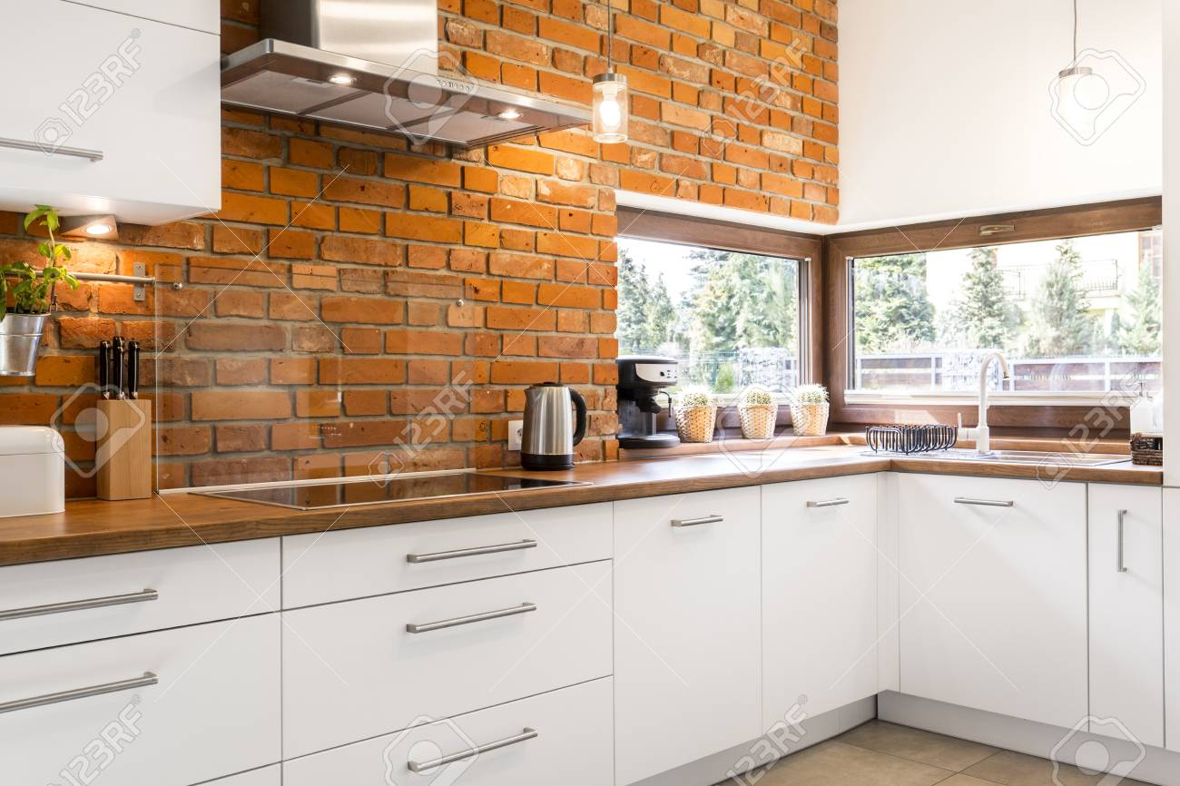 Picture of spacious kitchen with red brick wall