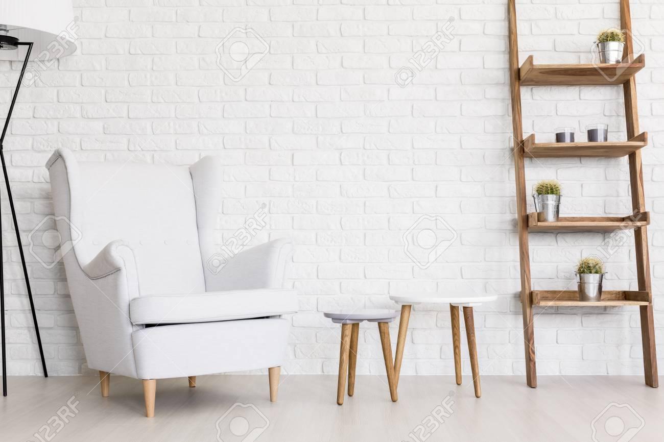 Coin salon très lumineux d\'un appartement contemporain avec un mur de  briques et une chaise aile blanche confortable