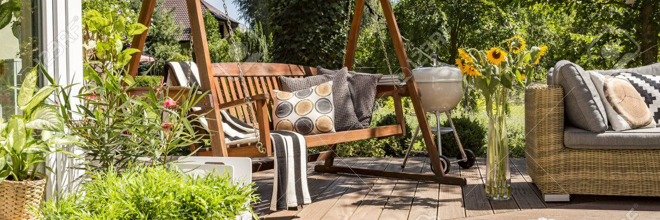 Cozy house terrace with wooden garden swing and a grill - 62746804