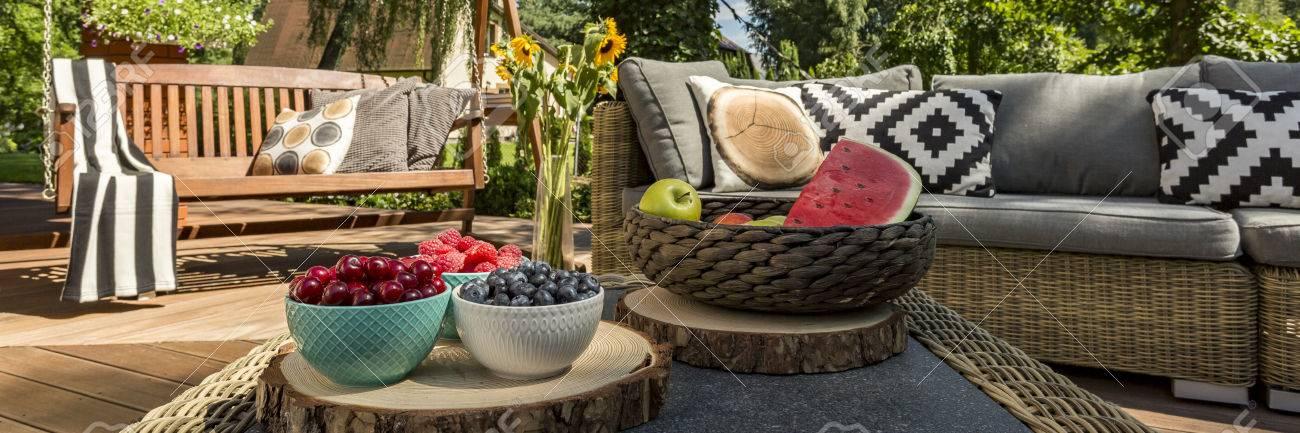 Véranda Cosy d\'une maison avec des meubles de jardin, balançoire et une  table basse avec des fruits