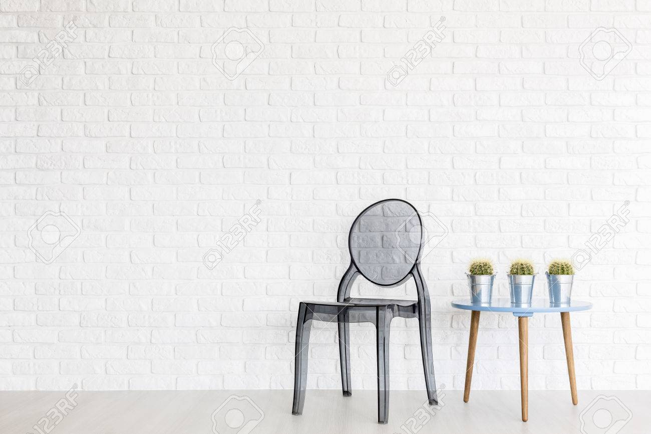 Ghost Chair And Designer Coffee Table In A Very Bright Interior With Brick  Wall Stock Photo