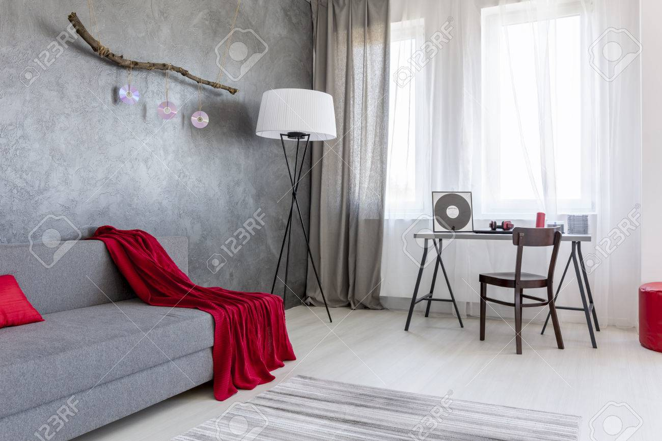 Pleasant Corner Of A Living Room Arranged In Grey With Red Accessories Stock Photo