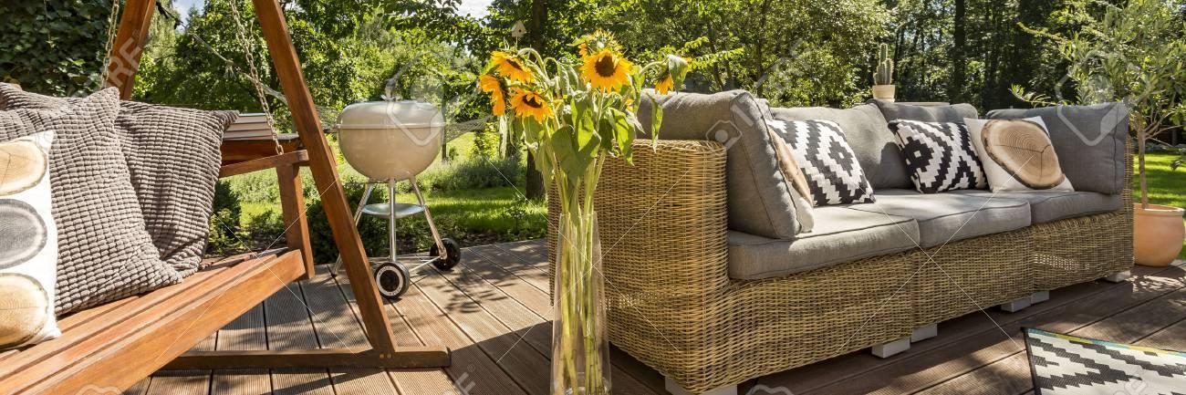 Spacieuse véranda extérieur de la maison avec furniteure de jardin et  balançoire en bois