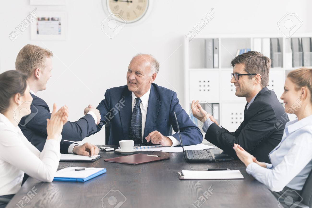 Business meeting at a large table, with a senior businessman shaking hands with a younger one - 62756468