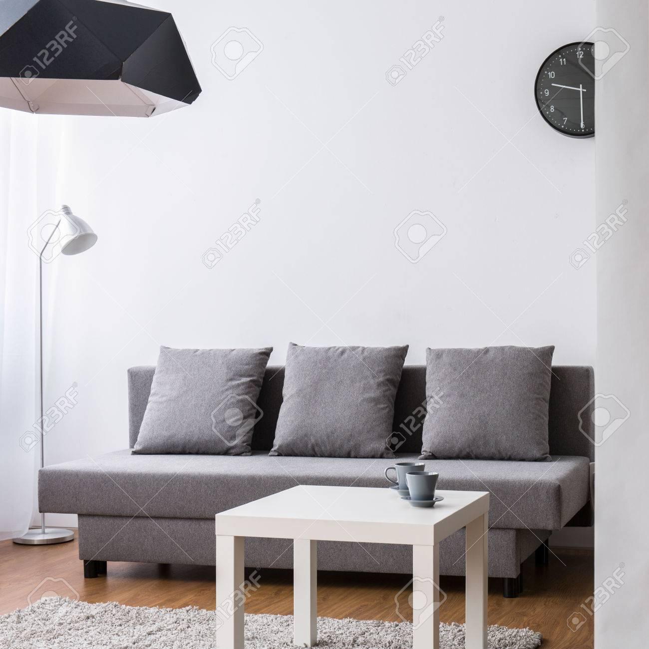 Soggiorno moderno con grande, divano grigio e tavolino da caffè. Luce  interna con carta da parati decorativi.