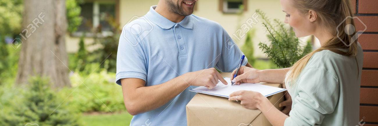 Young woman signing a delivery confirmation in front of her house Standard-Bild - 62764787