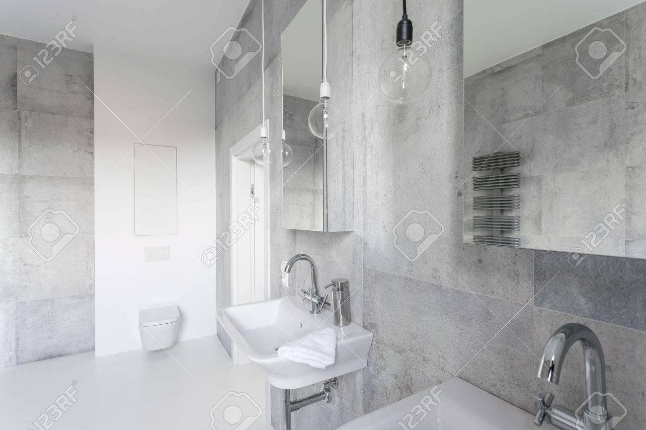 Salle de bains moderne décorée avec du béton gris et carreaux blancs et  d\'équipements sanitaires