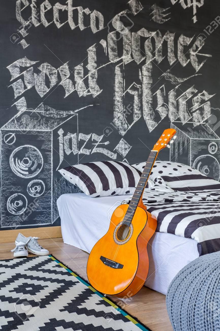 Chambre créative noir et blanc avec un mur tableau noir, une règle de  guitare à côté d\'un lit