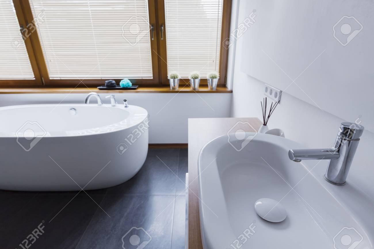 Moderne Badezimmer Mit Weißen Wänden, Dunklen Fliesen Auf Dem Boden,  Schneeweißen Badewanne, Waschbecken