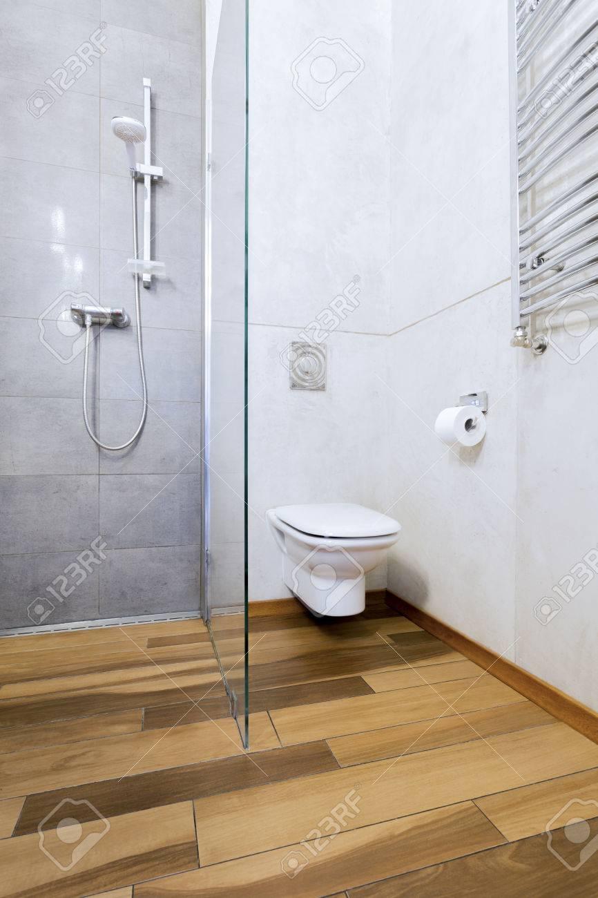 Intérieur Salle de bain avec moderne, parquet, carrelage blanc sur le mur,  toilettes et douche vitrée