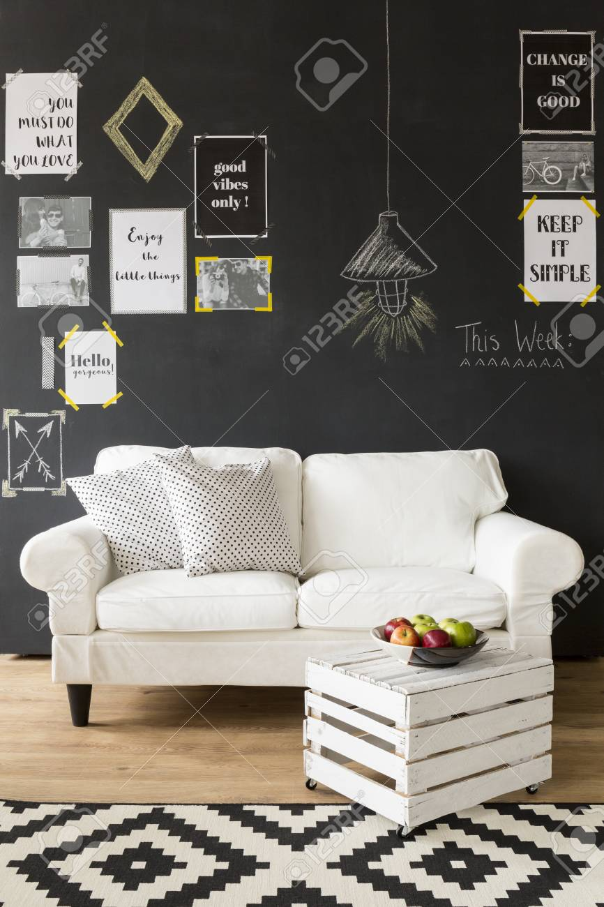Modern Gestaltete Innenraum Mit Einer Schwarzen Wand Mit Motivplakate Auf,  Weißen Couch Mit Kissen,