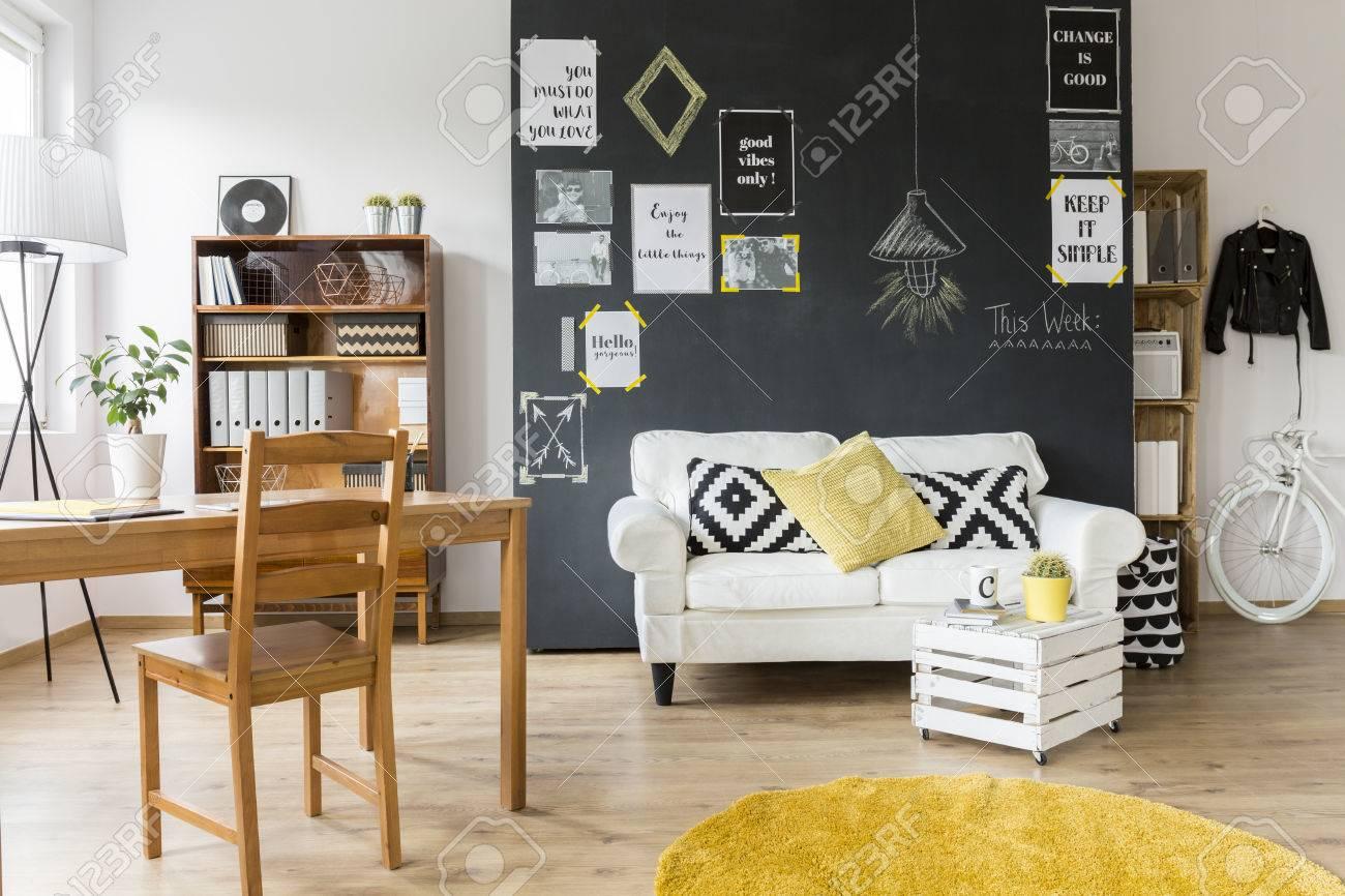 Chambre Avec Un Mur Noir cette chambre moderne conçue avec un mur noir avec des affiches de  motivation sur, avec table en bois, chaise, étagères, canapé blanc avec des
