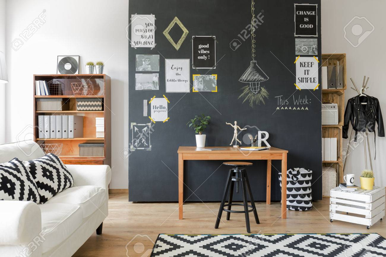 Cette chambre moderne conçue avec un mur noir avec des affiches de