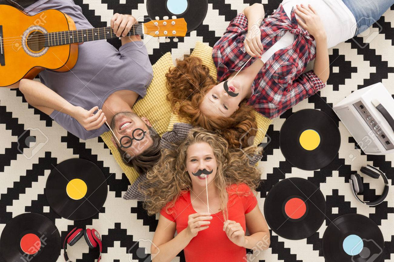 Top view of happy friends with funny photo props lying on a pattern background Stock Photo - 63932272