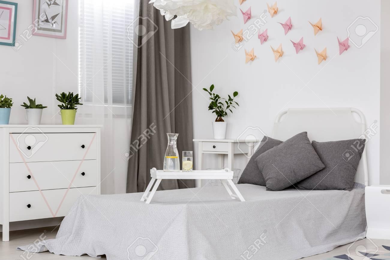 Chambre lumineuse avec lit simple, commode et décoration murale en origami  19D