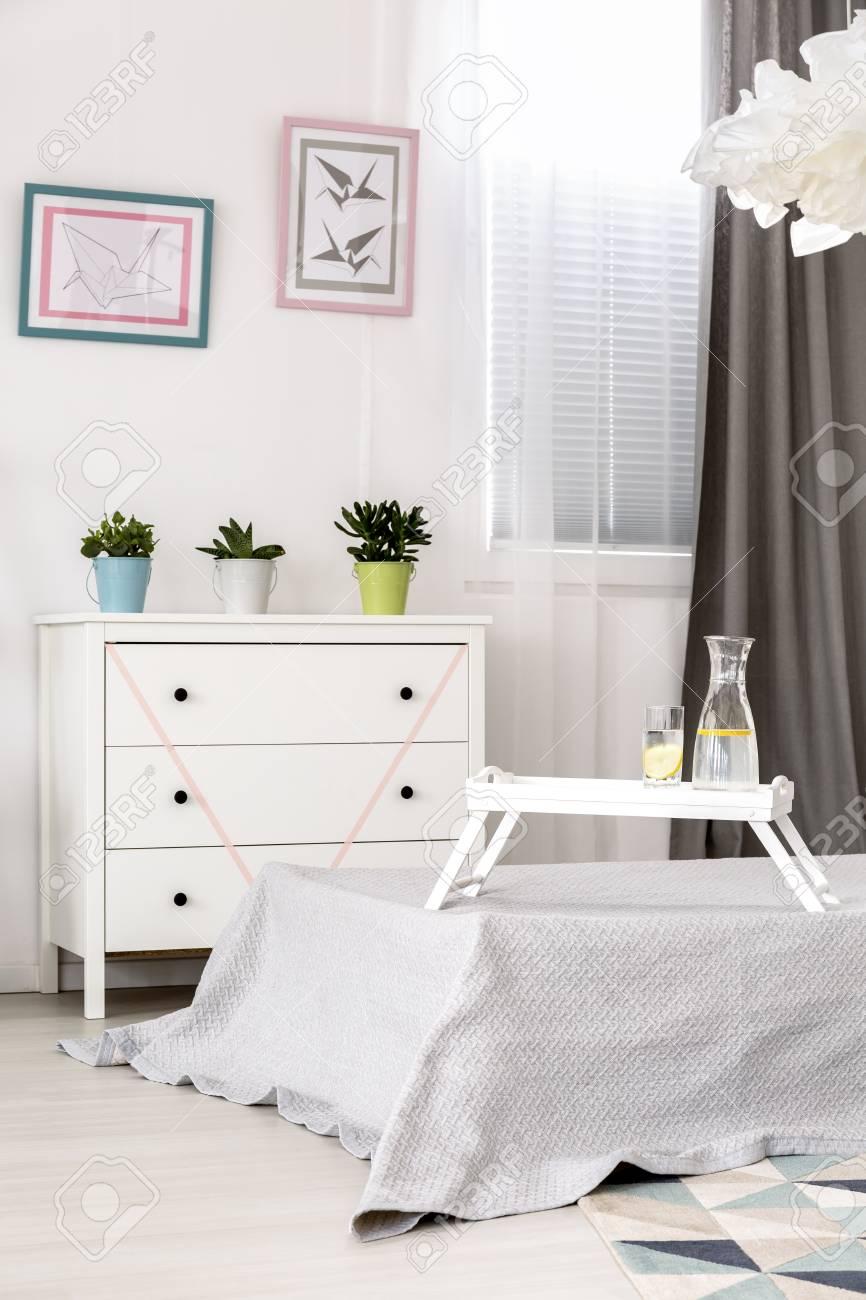 Camera da letto bianca con letto singolo, comò elegante e lampada a  sospensione origami