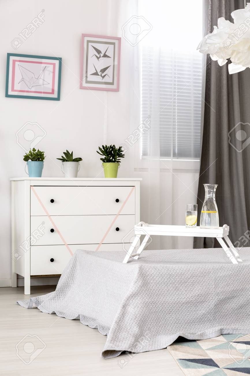 Chambre blanche avec lit simple, commode élégante et suspension en origami