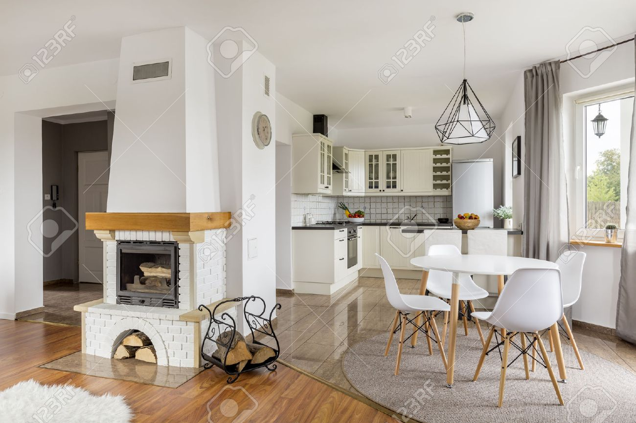 Open Floor Flat With Fireplace Dining Area And Light Kitchen Stock Photo