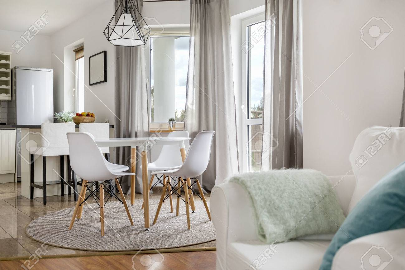 New flat with round table, white chairs and open kitchen Stock Photo - 63502531