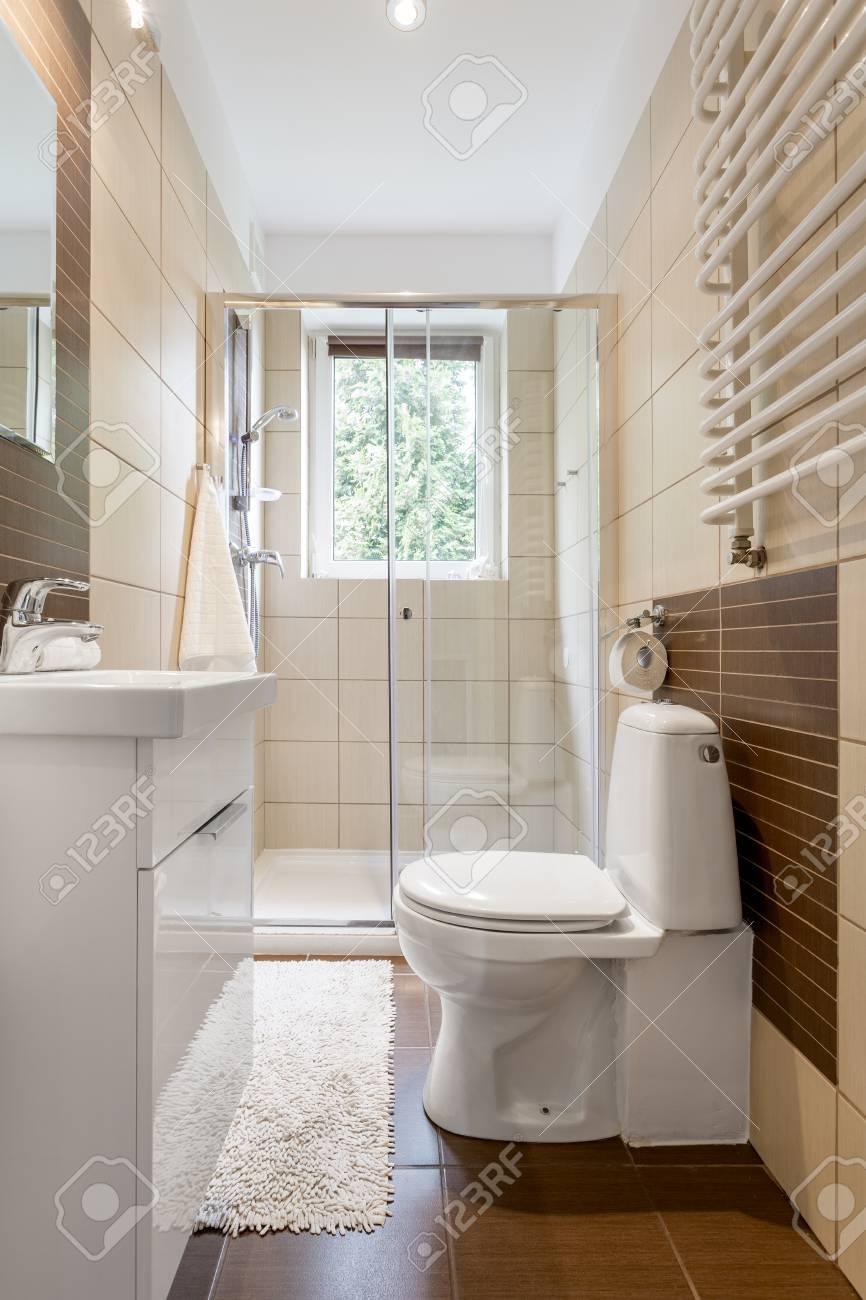 Pequeño cuarto de baño interior en marrón con ventana, baño, ducha y lavabo